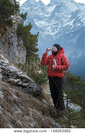 Mountaineer at winter snowy peaks background is resting and drinking from vacuum flask metal cup