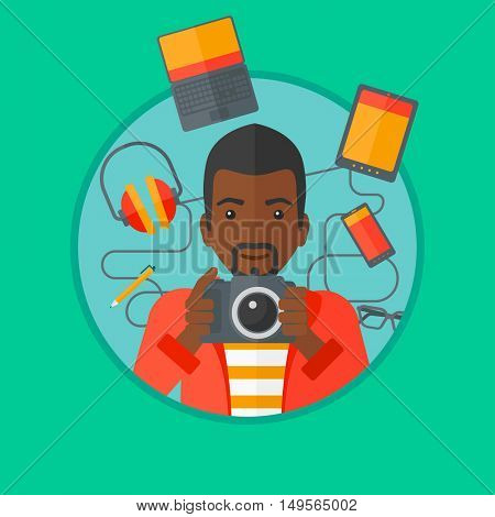An african-american man taking photo with digital camera. Young man surrounded with gadgets. Man using many electronic gadgets. Vector flat design illustration in the circle isolated on background.