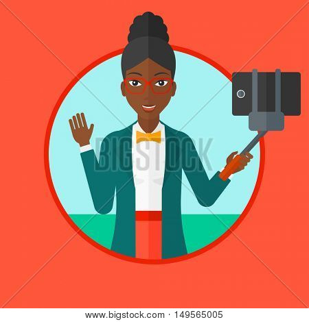 African-american woman making selfie with a selfie-stick. Woman taking photo with cellphone. Young woman taking selfie and waving. Vector flat design illustration in the circle isolated on background.