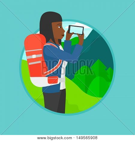 An african-american woman taking photo of landscape with mountains. Young woman with backpack taking photo with her cellphone. Vector flat design illustration in the circle isolated on background.