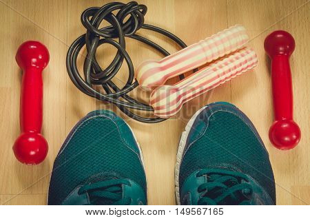 Fitness background with dumbbells skipping rope and athletic shoes.