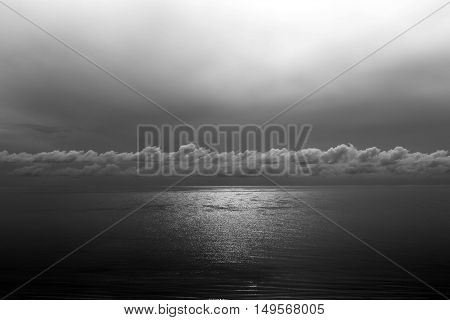 Top view of sun reflection ocean glistening with cloud toned in black and white