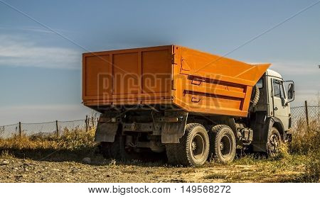 Lorry, truck, tip truck, tip lorry, dump truck, trucking industry, orange truck on a blue sky background