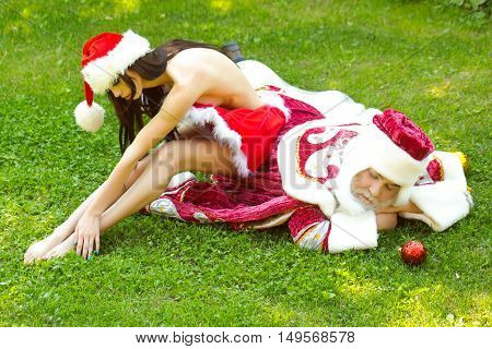Santa claus man and pretty sexy woman in Christmas new year red suit and hat rest on green grass on natural background