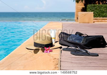 Hat beach bag sunglasses and flip flops next to swimming pool with beach background