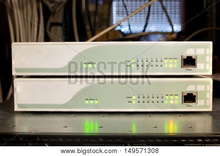 Two network routers with lights showing activity