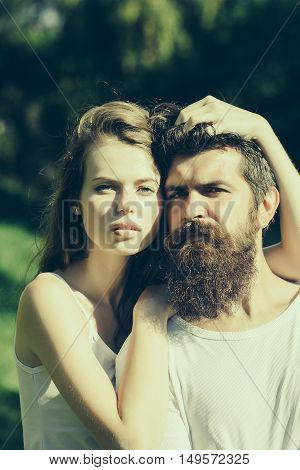 young couple of sexy woman with long blonde hair embracing bearded handsome man with beard and stylish hairstyle standing in lawn with green grass sunny summer outdoor