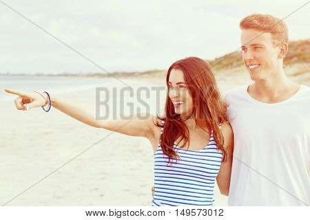 Happy young man and woman couple together walking on a beach