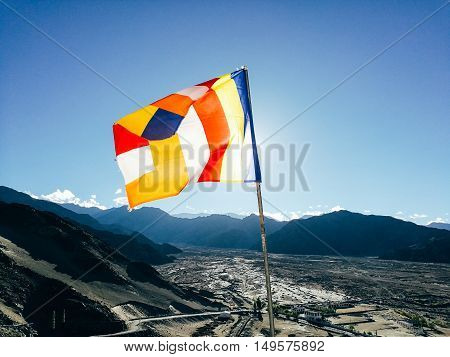 One Single Buddhist Prayer Flag In Six Colors Fluttering In Mountain Region Against The Sunlight. -