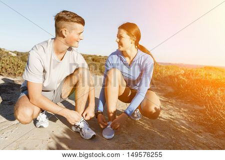 Couple of runners lace their shoes and prepare to jogging