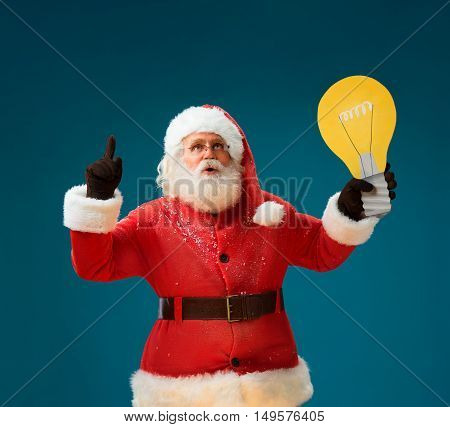 Creative Santa Claus showing light bulb banner looking happy excited. Thoughtful Santa Claus on blue background having idea