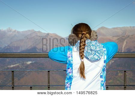Girl with a pigtail dressed in sports jacket and warm fluffy headphones admires of autumn mountain landscape views of hills and peaks of Caucasus mountains. Krasnaya Polyana - Alpine ski resort. Rosa Khutor Sochi Russia