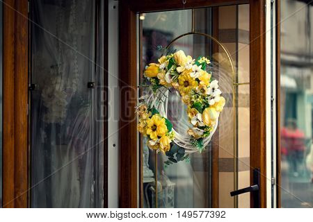 Wreath with different flowers on the door of the flower shop copy space