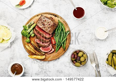 Rare steak with vegetable garnish and sauces for meat on white table top view