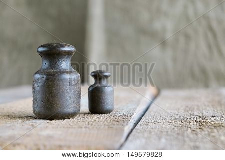 Two old weights on the old wooden table. Texture background exterior