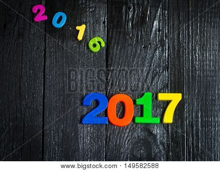 Expiring 2016.New year 2017multi-colored figures on a wooden black background.