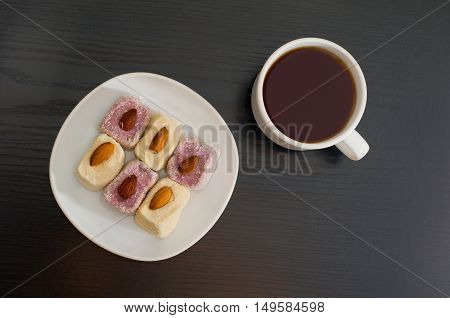 Mug of tea and Turkish Delight with almonds on a plate top view black background