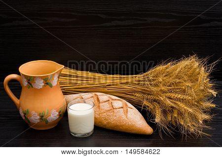 Jug glass of milk a loaf of rye and a sheaf on a black background