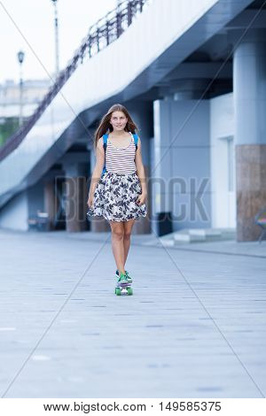 Young Cute School Girl Rides Skateboard On Road