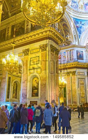 SAINT PETERSBURG RUSSIA - APRIL 25 2015: The tourists from all over the world visit St Isaac's Cathedral and admire its beauty on April 25 in Saint Petersburg.