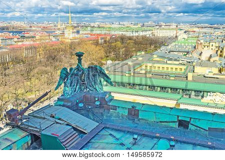 The bronze Angels on St Isaac's Cathedral roof with the trees of Alexander Garden golden spire of Admiralty Building and granite Alexander Column in the Palace Square on the background St Petersburg Russia.