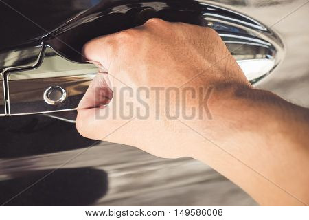 Hand on handle. Closeup of Businessman opening car door.