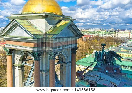 The stone bell tower of St Isaac's Cathedral decorated with granite columns with bronze capitals and the golden dome shining brightly on the sun St Petersburg Russia.