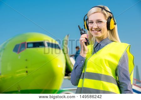 Aircraft worker with radio standing in front of a commercial airliner