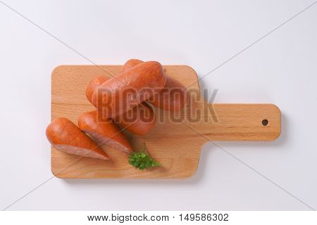whole and sliced short sausages on wooden cutting board
