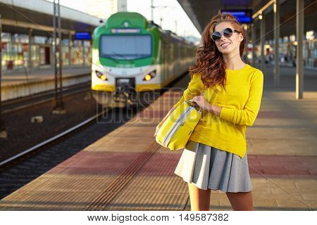 caucasian woman waiting at the railway station with a suitcase.