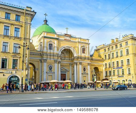SAINT PETERSBURG RUSSIA - APRIL 25 2015: The facade of Catholic Church of St Catherine with monumental arched portal on self-supporting columns and the massive green cupola located in Nevsky Prospekt on April 25 in Saint Petersburg.