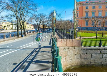 SAINT PETERSBURG RUSSIA - APRIL 25 2015: The walk along the First Engineer Bridge over Moyka River with the bright orange wall of St Michael's Castle on the background on April 25 in Saint Petersburg.