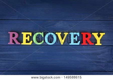 Word RECOVERY made of colourful letters on blue wooden background
