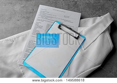 Medical service concept. Visiting card and clipboard on doctor uniform