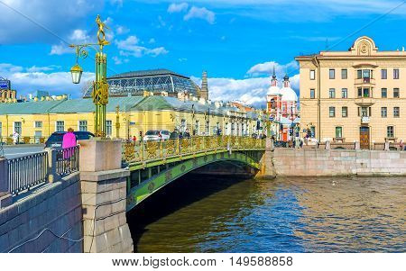 SAINT PETERSBURG RUSSIA - APRIL 25 2015: The beautiful Panteleimonovsky Bridge over Fontanka River decorated with gilt patterns sculptures and lanterns and leads to the Church of Holy Great Martyr and Healer Panteleimon on April 25 in Saint Petersburg.
