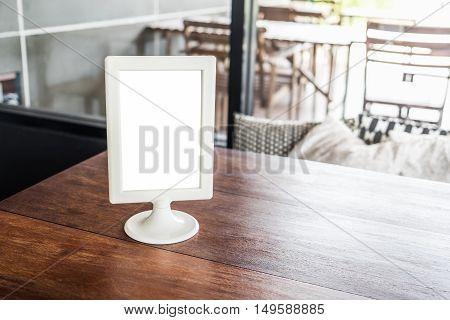 Mock up menu frame on wooden table in cafe or restaurant interior background.