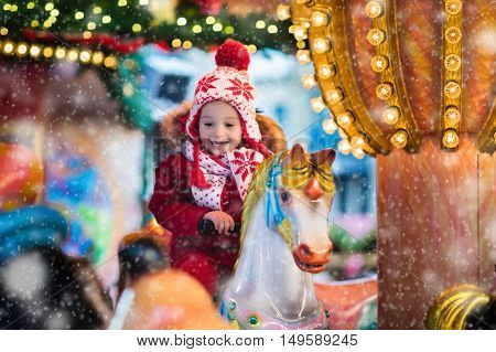 Happy little boy in warm jacket and red knitted Nordic hat and scarf riding carousel horse during family trip to traditional German Christmas market. Kids at Xmas outdoor fair on snowy winter day.