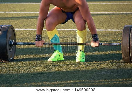 Man practicing weight lifting out on the pitch