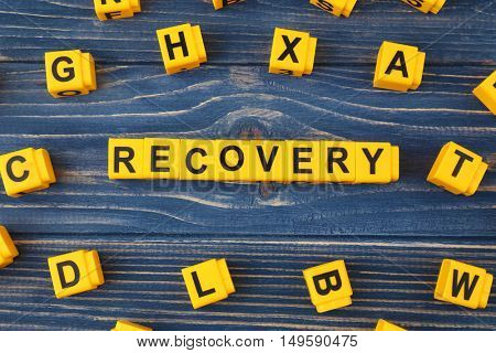 Medical concept. Word RECOVERY made of yellow cubes on blue wooden background