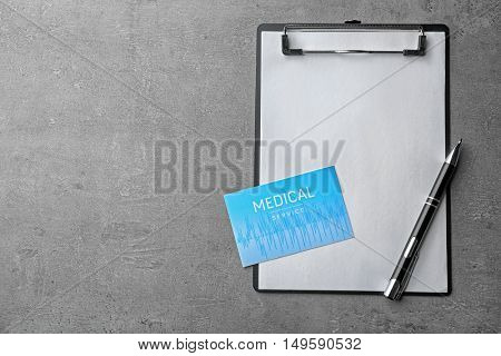 Medical service concept. Visiting card, clipboard and pen on grey background