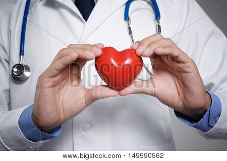 Male doctor holding red heart, closeup