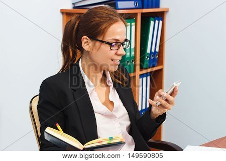 Woman Holds A Phone And A Datebook