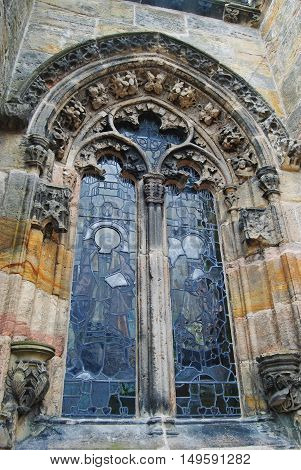 Roslin, United Kingdom - June 18, 2014. Ornate window of Rosslyn Chapel, with floral sculptures and religious frescoes.