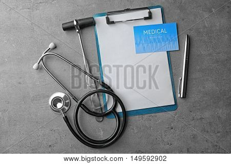 Health care concept. Visiting card, clipboard and medical equipment on grey background