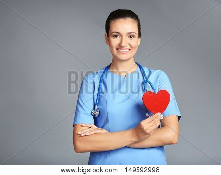 Portrait of doctor cardiologist with red heart in hand on grey background