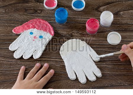 Child Paints Acrylic Paints Christmas Toy From The Salty Test Frost Grandfather. Children's Art Proj