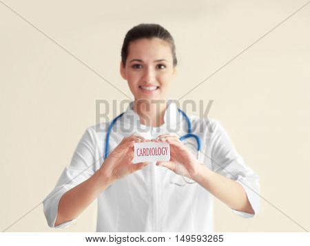 Doctor holding card with word CARDIOLOGY on white wall background