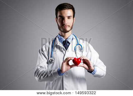 Handsome male doctor holding red heart on grey background