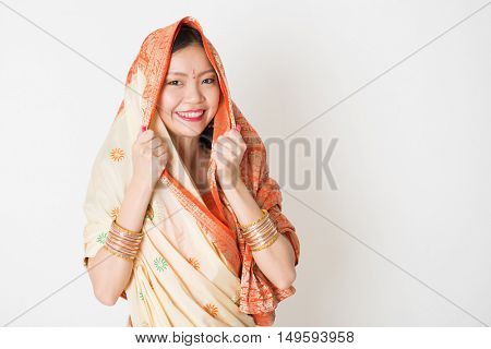 Portrait of young mixed race Indian Chinese woman in traditional sari dress smiling and looking at camera, with plain background.