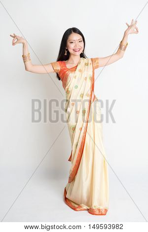 Portrait of young mixed race Indian Chinese female in traditional sari dress dancing, full length on plain background.